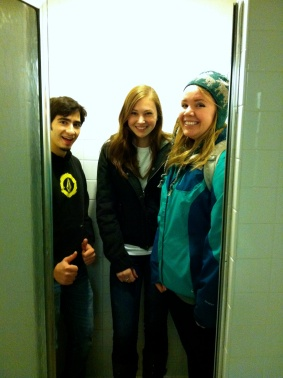 Emir, Sarah, and Elyse pose in a shower during a scavenger hunt.